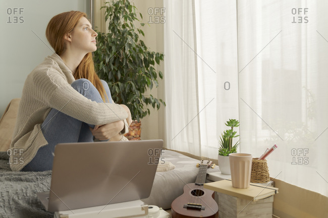 Serious young woman at home looking out of window