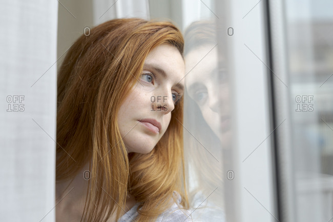 Portrait of serious young woman looking out of window