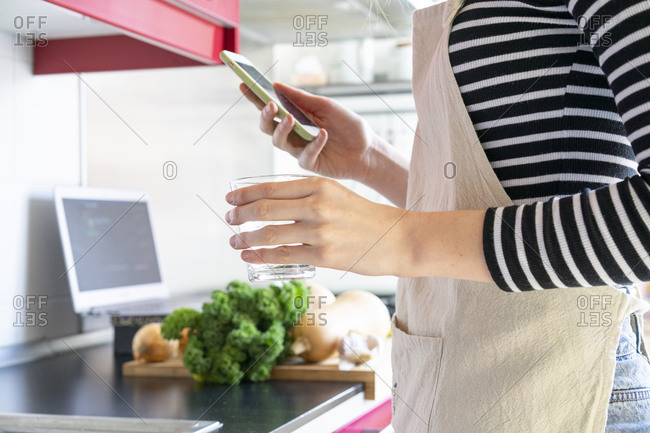 Young woman preparing healthy meal- using smartphone