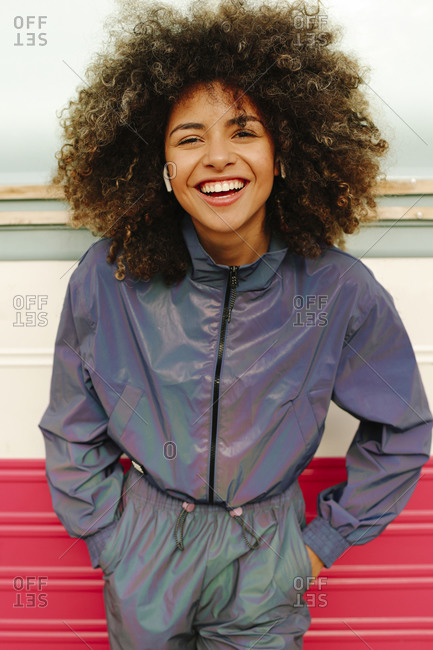 Portrait of happy stylish young woman wearing tracksuit outdoors