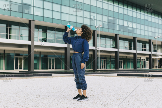 Sporty young woman having a cooling break in front of modern building
