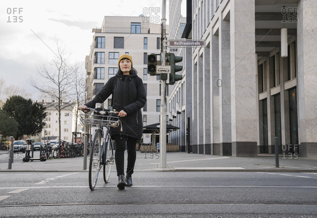 Woman with bicycle in the city on the go- Frankfurt- Germany