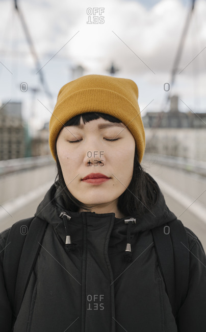 Portrait of woman with closed eyes on a bridge