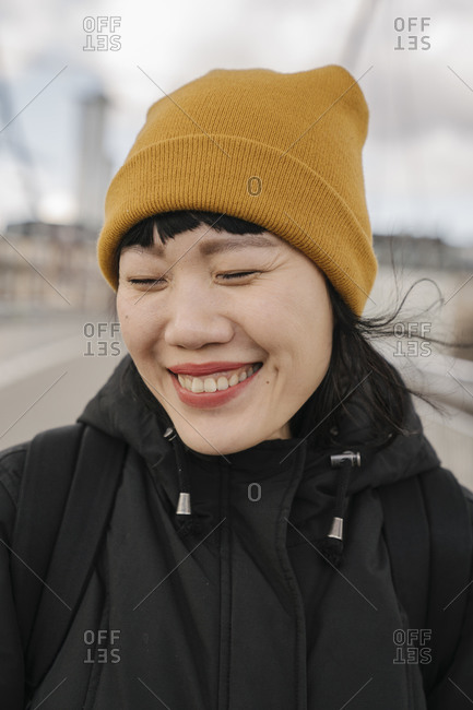 Portrait of happy woman with closed eyes on a bridge