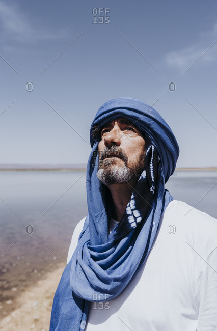 Man in the desert of Merzouga standing in front of lake- Morocco