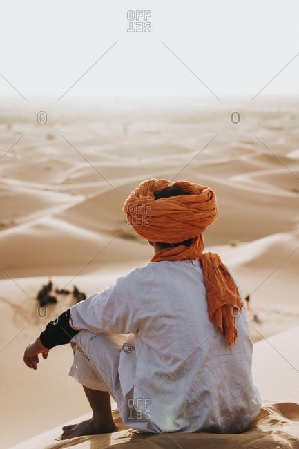 Back view of man sitting in Merzouga desert- Morocco