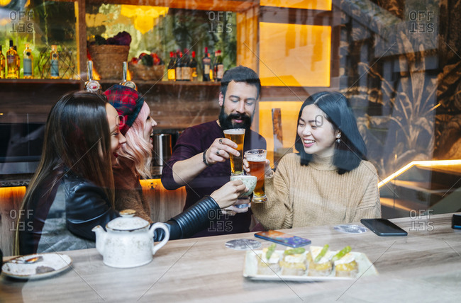 Friends meeting in a trendy bar- clinking glasses