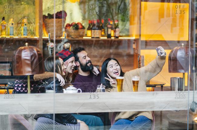 Friends meeting in a trendy bar- taking smartphone selfies