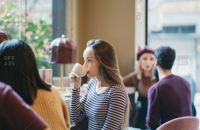 Young woman sitting in busy bar of a restaurant- drinking coffee