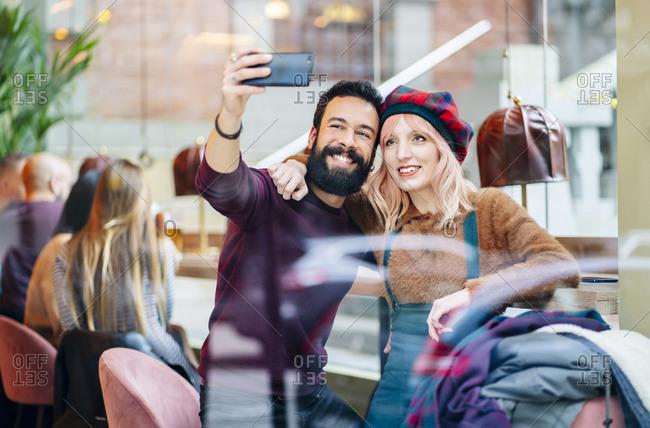 Friends meeting in a trendy bar- couple taking selfies