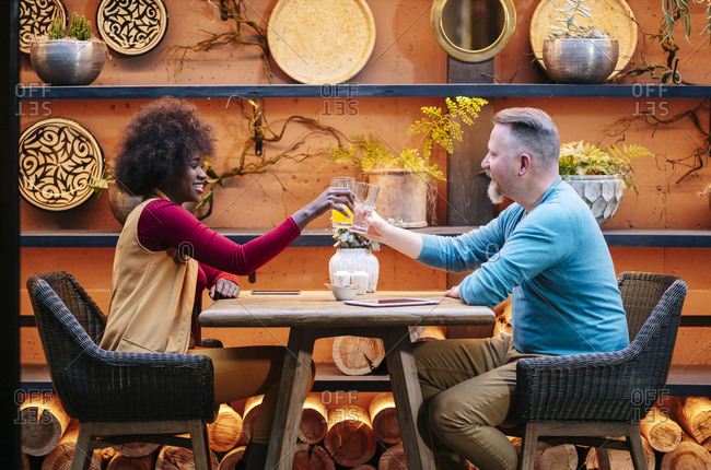 Man and woman having drinks in a restaurant- toasting