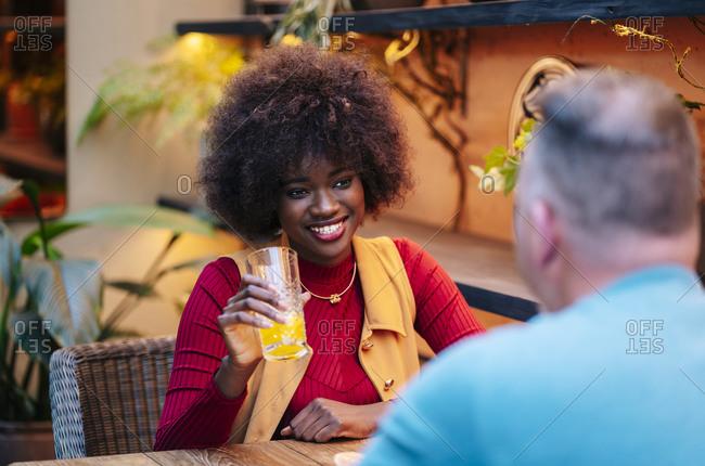 Man and woman having drinks in a restaurant- talking