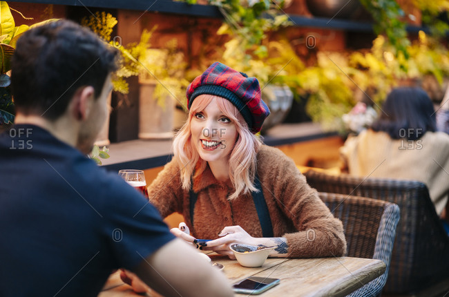 Man and woman having drinks in a restaurant- using smartphone