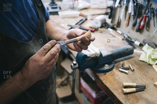 Craftsman making knives in his workshop