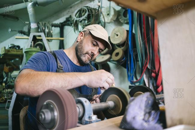 Portrait of focused craftsman making knives in his workshop