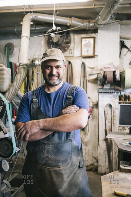 Portrait of a confident knife maker in his workshop