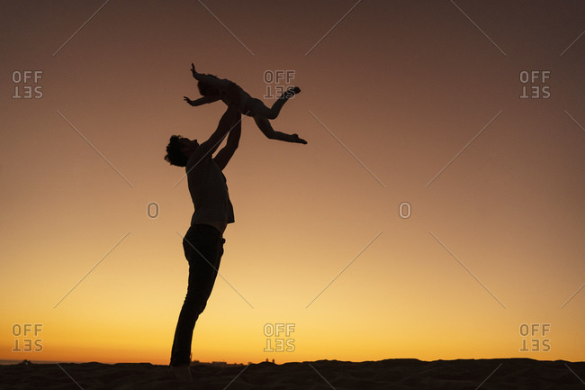 Father playing with daughter on sand dune at sunset- Gran Canaria- Spain