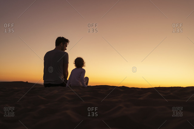 Father sitting with daughter in sand dunes at sunset- Gran Canaria- Spain