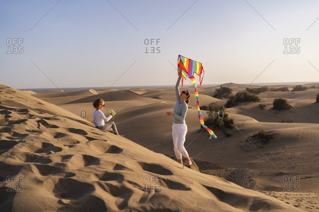 Mother and daughter flying kite in sand dunes- Gran Canaria- Spain
