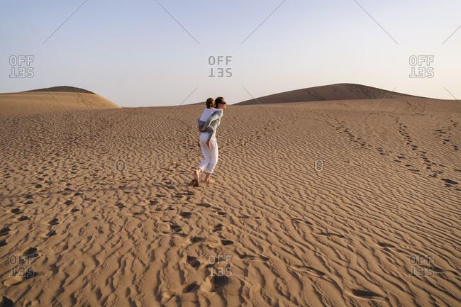 Mother carrying daughter piggyback in sand dunes- Gran Canaria- Spain