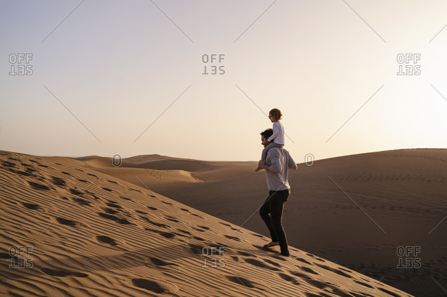 Father carrying daughter on shoulders in sand dunes- Gran Canaria- Spain