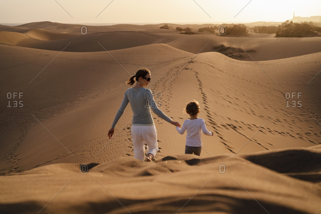 Mother and daughter walking hand in hand in sand dunes- Gran Canaria- Spain