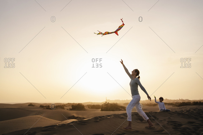 Mother and daughter flying kite in sand dunes at sunset- Gran Canaria- Spain