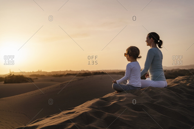 Mother and daughter practicing yoga in sand dunes at sunset- Gran Canaria- Spain