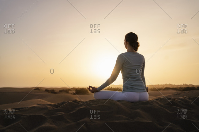 Woman practicing yoga in sand dunes at sunset- Gran Canaria- Spain