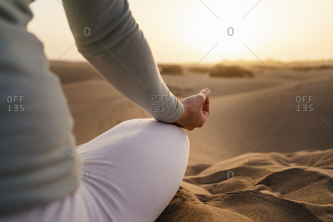 Close-up of woman practicing yoga in sand dunes at sunset- Gran Canaria- Spain