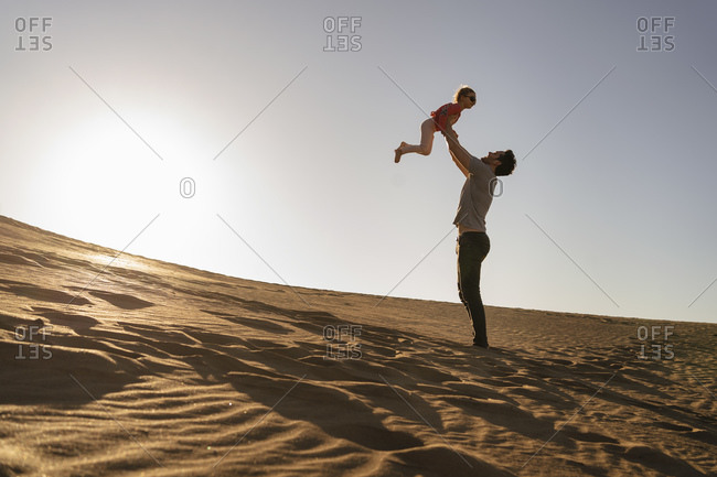 Father playing with daughter in sand dune at sunset- Gran Canaria- Spain