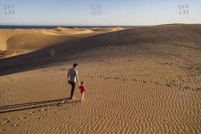 Father and daughter walking hand in hand in sand dunes- Gran Canaria- Spain