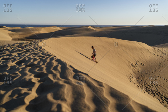 Father and daughter walking up sand dune- Gran Canaria- Spain