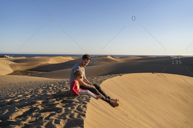 Father and daughter sitting on sand dune- Gran Canaria- Spain