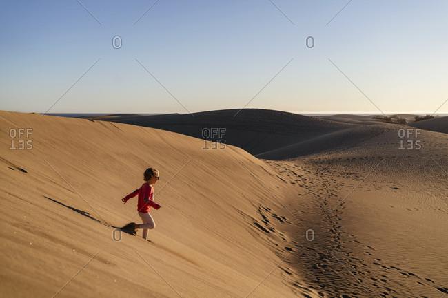 Girl running down sand dune- Gran Canaria- Spain