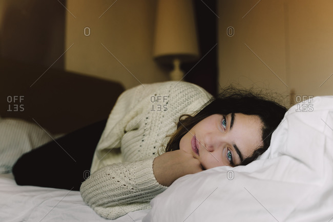 Portrait of pensive girl lying on bed looking at distance