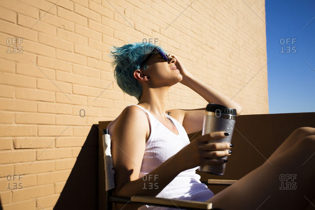 Young woman with blue hair pouring water over her head on balcony