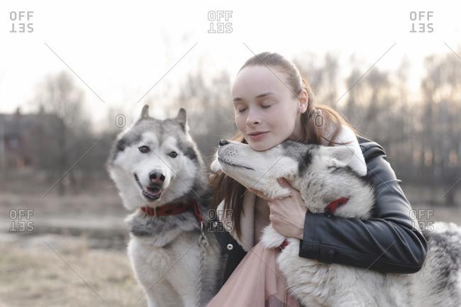 Portrait of woman cuddling husky