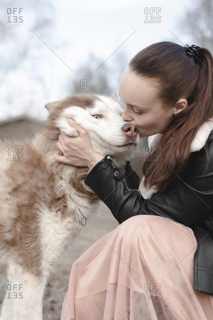 Woman kissing her husky dog