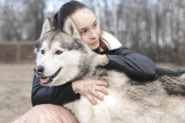 Portrait of happy woman cuddling her husky
