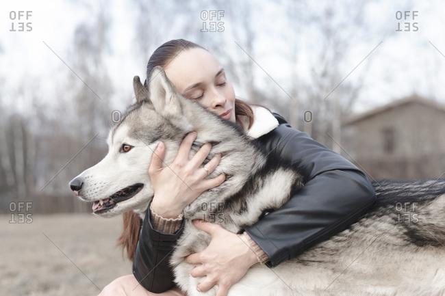 Happy woman cuddling her dog
