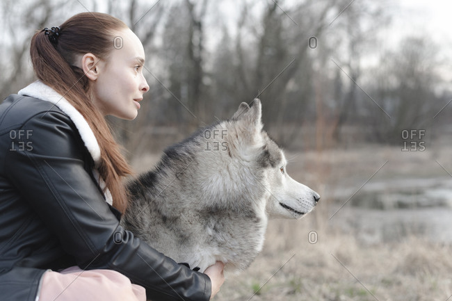 Woman and her husky looking at distance