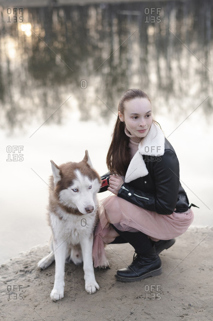 Portrait of woman and her husky at water's edge