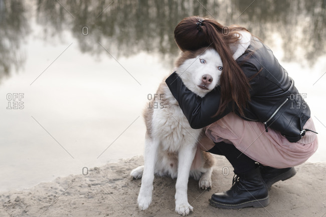 Woman hugging her husky at water's edge