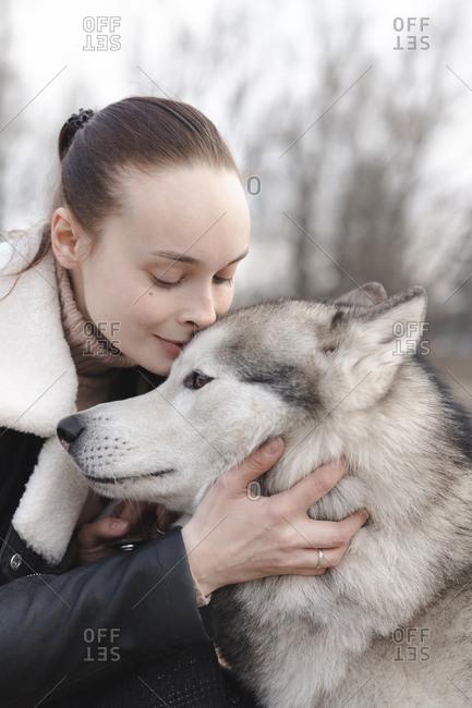Portrait of woman cuddling her husky