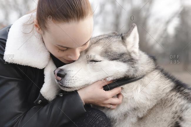 Woman cuddling her husky dog