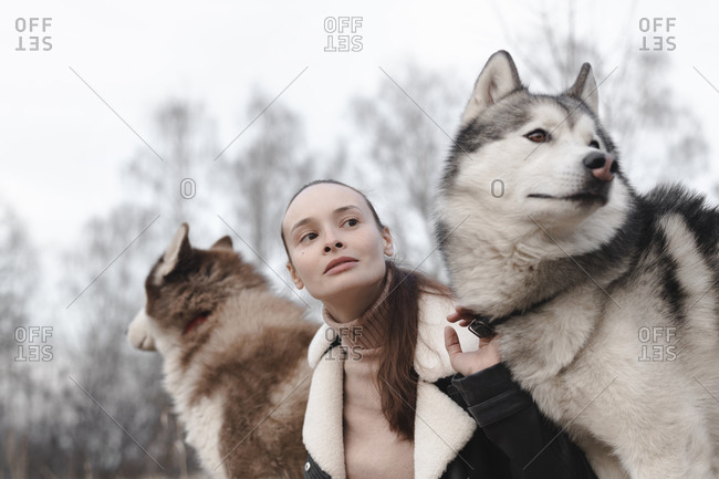 Portrait of woman with two huskies watching something