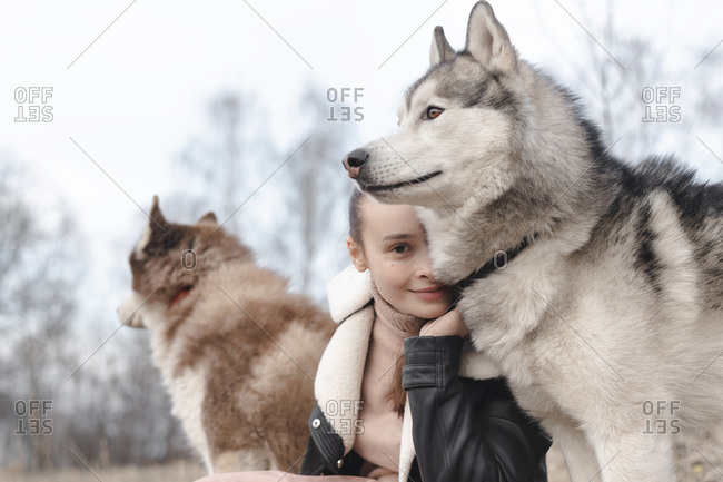 Portrait of smiling woman with her huskies