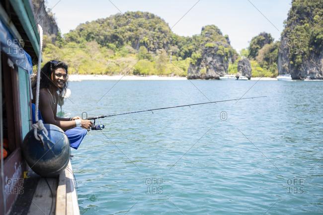 Young native man fishing on a boat trip- Ko Yao Yai- Thailand
