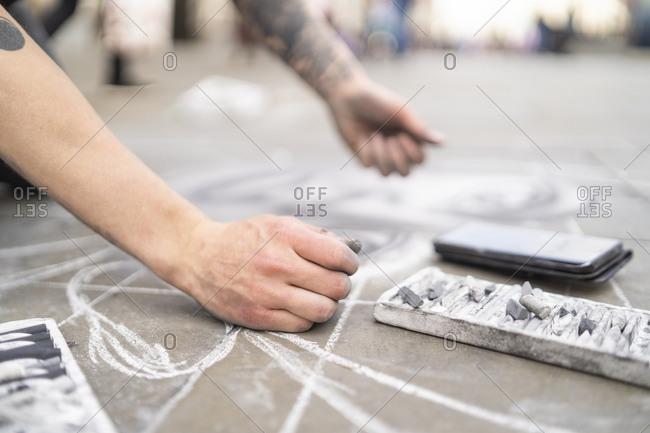 Street art- pavement artist drawing on pavement and using smartphone